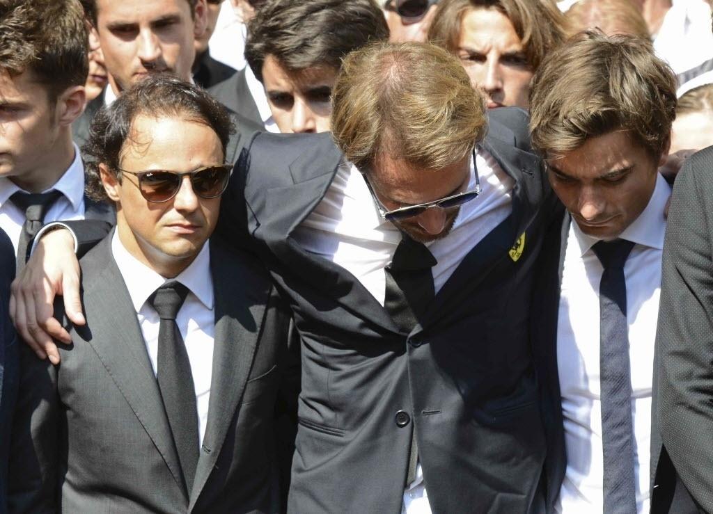 Felipe Massa (esquerda), Jean-Eric Vergne (centro) e um familiar de Bianchi se abraçam em frente ao caixão