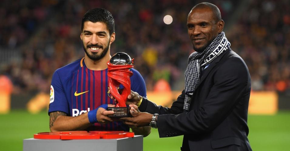 Ex-jogador do Barcelona, o francês Eric Abidal (dir.) entrega prêmio a Luis Suárez
