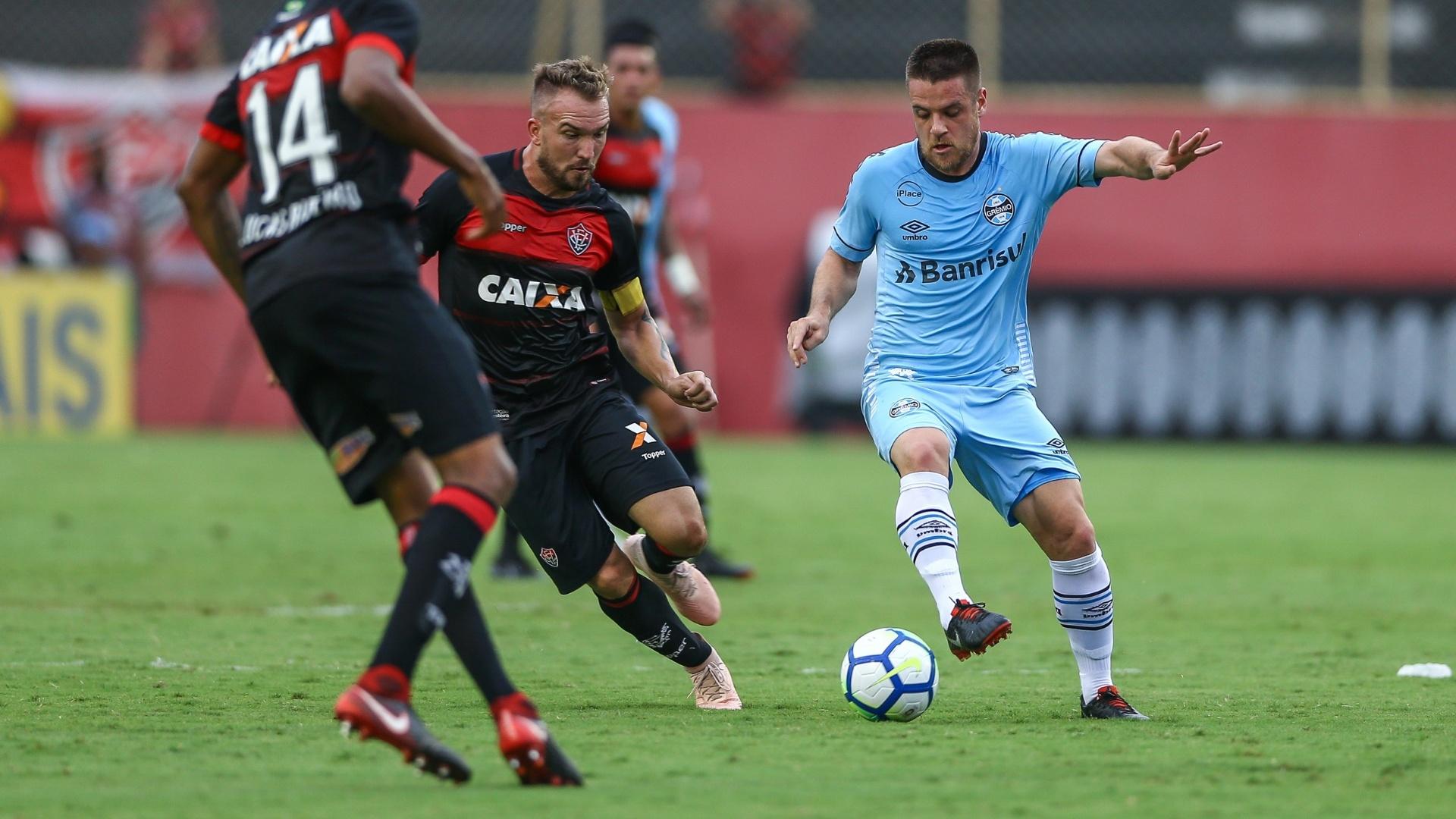 Ramiro, meio-campista do Grêmio, tenta se livrar da marcação do time do Vitória
