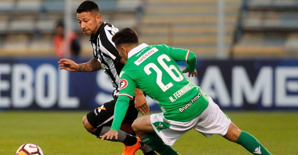 Leo Valencia passa pela marcação de Nicolas Fernandez no duelo entre Audax Italiano e Botafogo