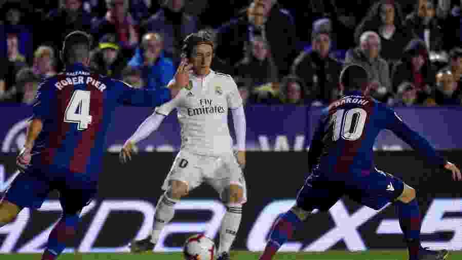 Luka Modric é marcado por jogadores do Levante  -  JOSE JORDAN / AFP