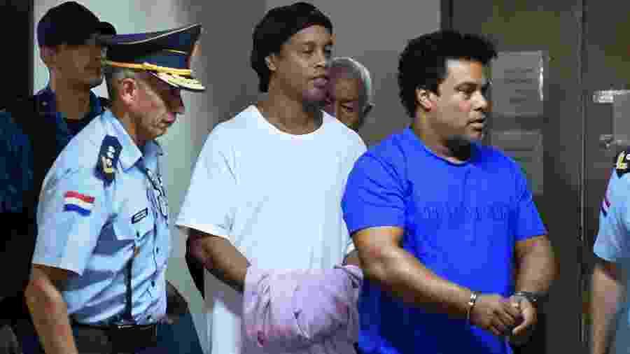 Ronaldinho e Assis chegam algemados para audiência de custódia - NORBERTO DUARTE/AFP