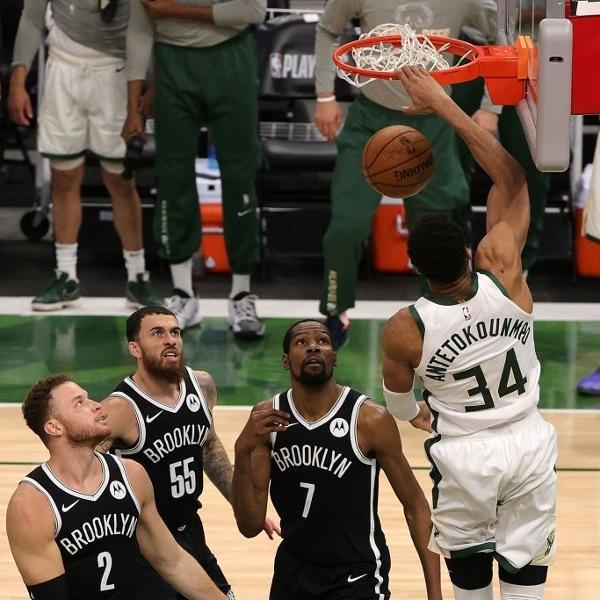 Giannis Antetokounmpo, do Milwaukee Bucks, enterra enquanto jogadores do Brooklyn Nets observam