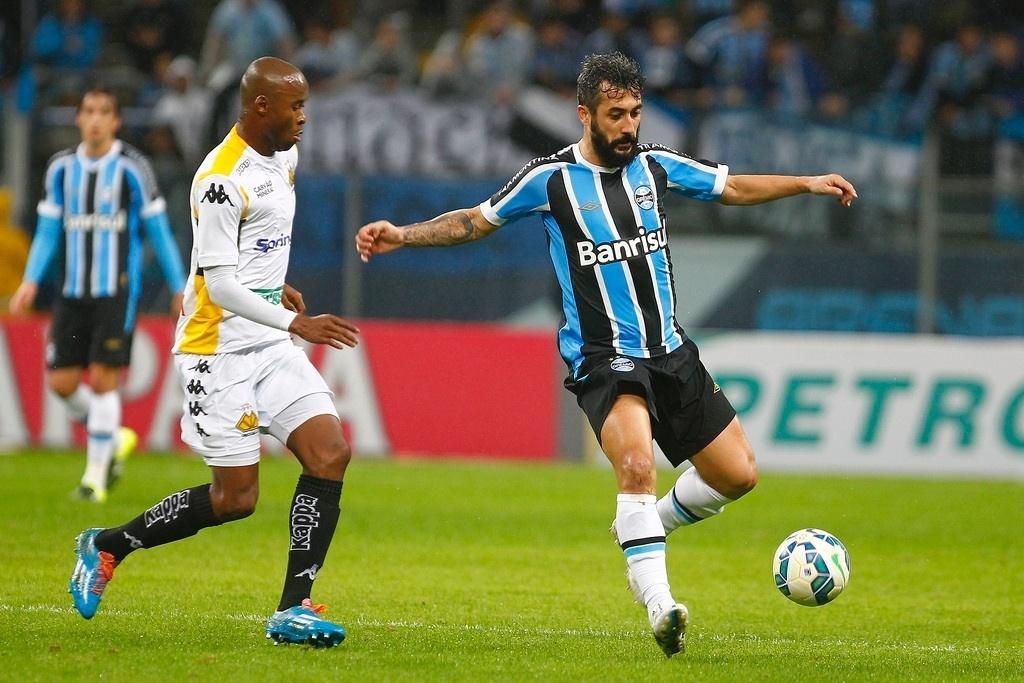 Meia Douglas recebe a marcação adversária n jogo entre Grêmio e Criciúma, na Copa do Brasil