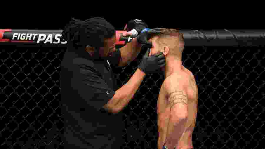O árbitro Herb Dean analisa o olho de Jeremy Stephens após o atleta levar uma dedada acidental de Yair Rodriguez - Josh Hedges/Zuffa LLC/Getty Images