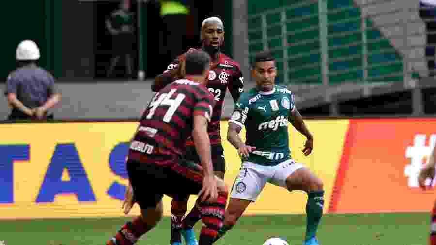 Dudu, marcado por Gerson, em ação no duelo Palmeiras x Flamengo: clubes lideram investimentos no Brasil - Bruno Ulivieri/AGIF