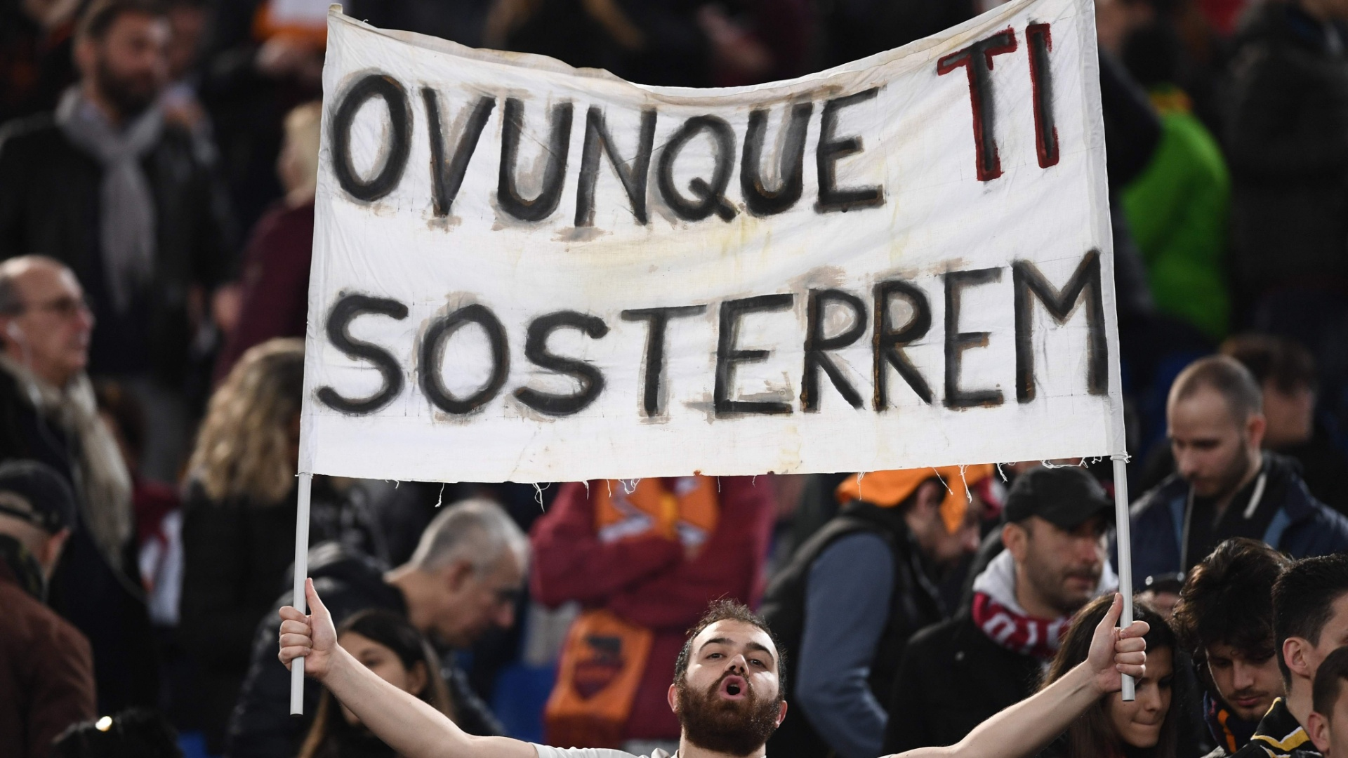 Torcedor exibe placa de apoio à Roma antes de jogo com o Barcelona