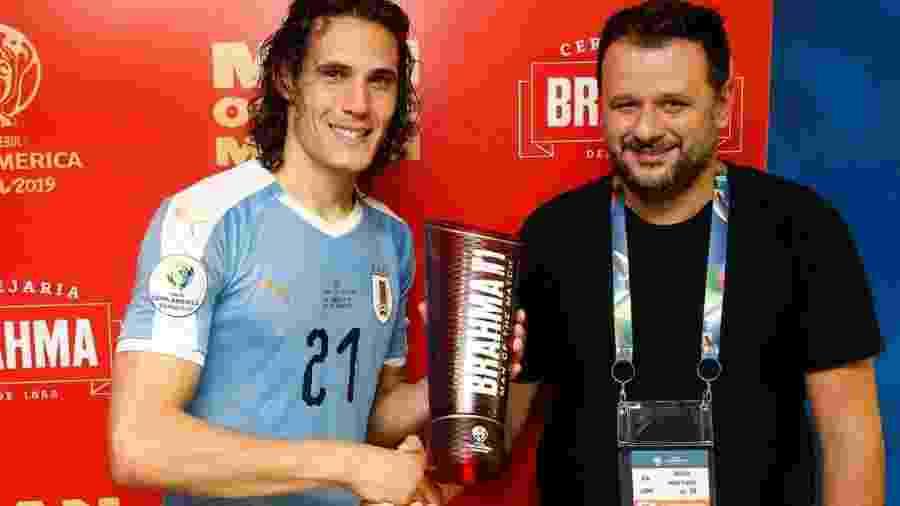 Cavani (e) recebe o prêmio de melhor em campo das mãos de Toninho, dono do Bar do Momo (RJ), após jogo no Maracanã - Staff Images/Conmebol