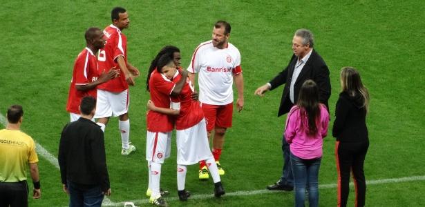 Filho de Fernandão, ao centro, abraça Tinga antes de participar de jogo festivo