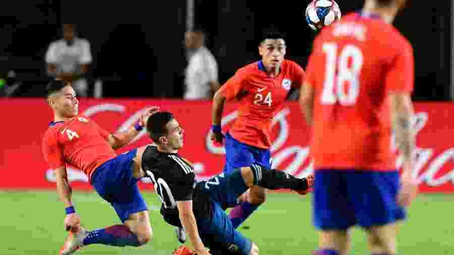 Lo Celso e Oscar Opazo disputam a bola em jogo amistoso  - Frederic J. BROWN / AFP