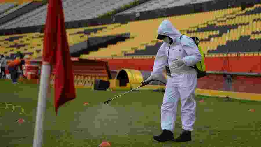 Funcionário desinfecta Estádio Monumental de Guayaquil antes de Barcelona (EQU) x Flamengo, ontem (22) - RODRIGO BUENDIA / POOL / AFP