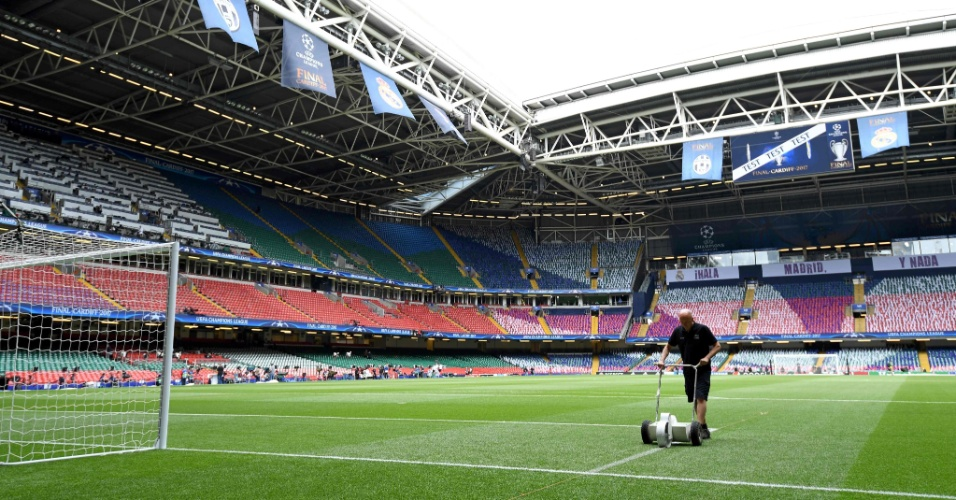 Funcionário do estádio de Cardiff demarca a linha de uma das áreas do campo antes da partida entre Real Madrid e Juventus