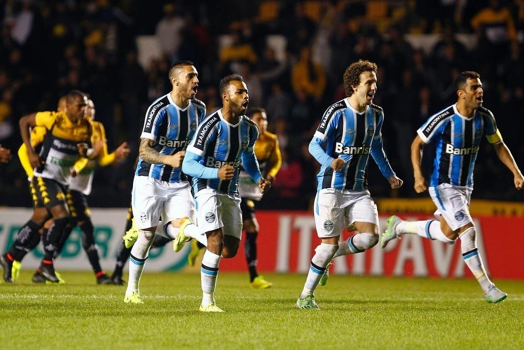 Atletas do Grêmio correm para abraçar o goleiro Marcelo Grohe, que defendeu o último pênalti da decisão contra o Criciúma