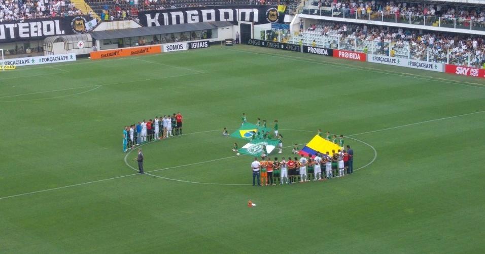 No gramado da Vila Belmiro, bandeiras do Brasil, da Colômbia e da Chapecoense são exibidas no gramado antes da partida Santos x América-MG; jogadores das duas equipes se perfilam no círculo central durante minuto de silêncio