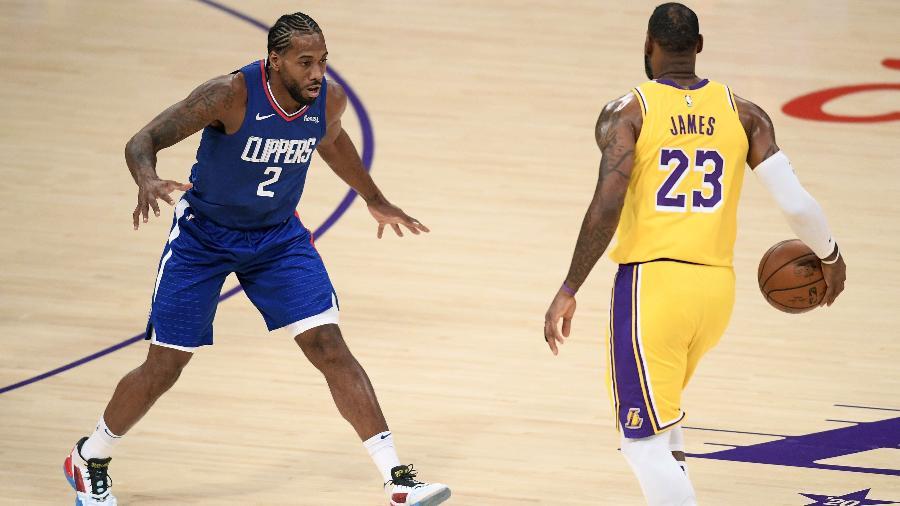 LeBron James, do Los Angeles Lakers, encara a marcação de Kawhi Leonard, do Los Angeles Clippers - Harry How/Getty Images/AFP