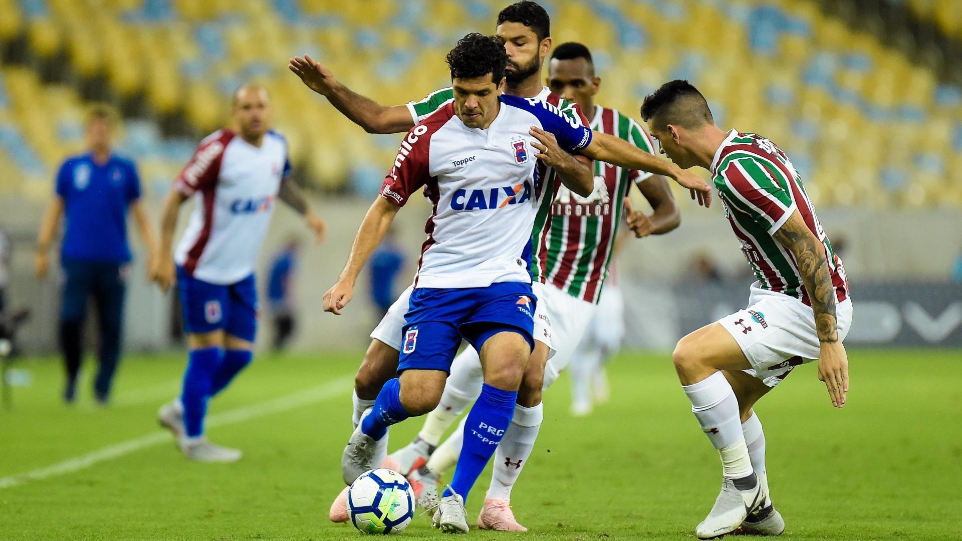 Ortigoza tenta fugir da marcação de Gum e Ibañez durante Fluminense x Paraná