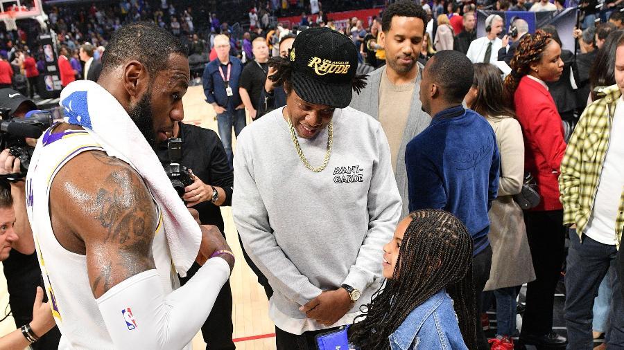 Jay-Z e a filha Blue Ivy Carter conversam com LeBron James depois do jogo entre Clippers e Lakers  - Allen Berezovsky/Getty Images