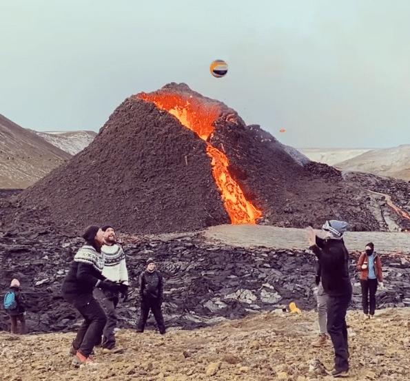 Grupo joga vôlei próximo a vulcão em erupção