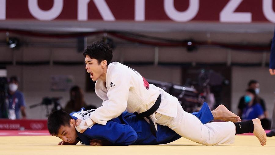 Brasileiro Eric Takabatake, de azul, sofre golpe do sul-coreano Kim Won Jin nas Olimpíadas de Tóquio - Jack Guez/AFP