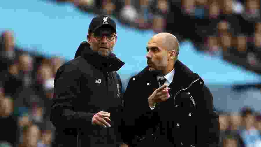 Jurgen Klopp e Pep Guardiola conversam durante a partida entre Manchester City x Liverpool - Matthew Ashton/AMA/Getty Images