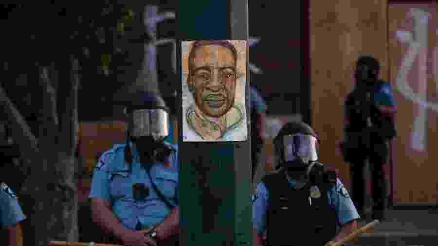 Policiais se posicionam ao lado de poste com desenho de George Floyd - Stephen Maturen/Getty Images