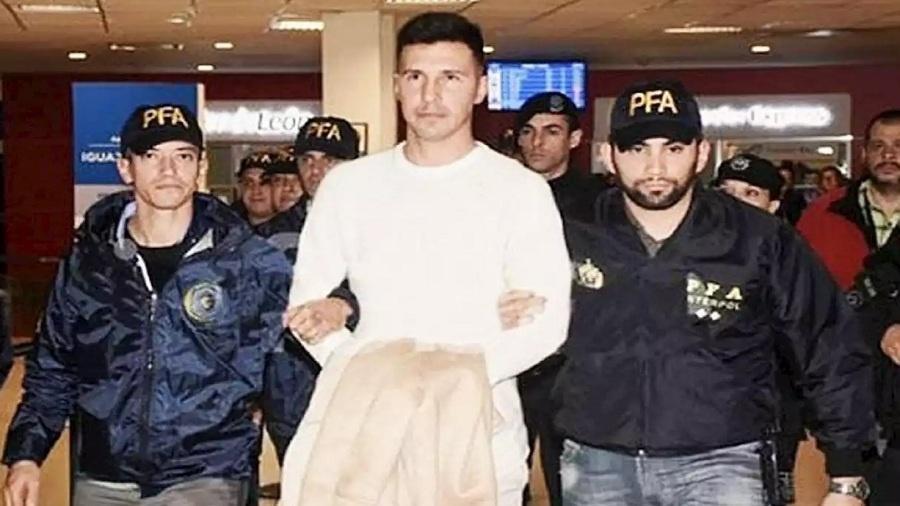 """Jonathan Fabbro é levado por policiais no Aeroporto de Buenos Aires - Reprodução jornal """"Crónica"""""""