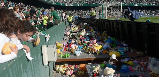 Crianças observam bichinhos de pelúcia que foram arremessados no estádio - CRISTINA QUICLER/AFP