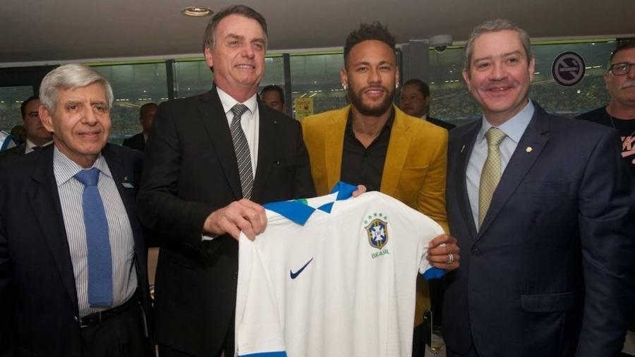 O presidente Jair Bolsonaro exibe uma camisa da seleção brasileira ao lado de Neymar, do presidente da CBF, Rogério Caboclo, e do general Augusto Heleno, chefe do GSI - Divulgação