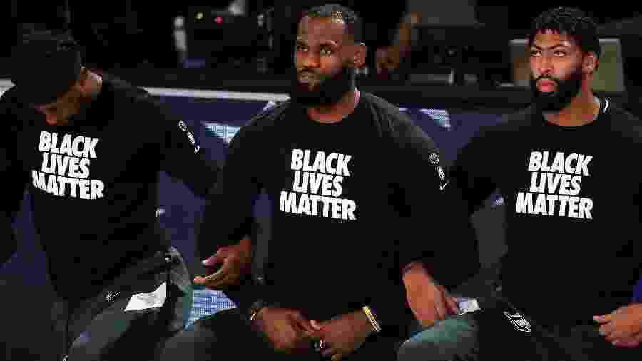 LeBron James (ao centro) se ajoelha durante execução do hino nacional americano em protesto antirracista - Mike Ehrmann/Getty Images/AFP