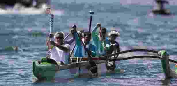 03.mai.2016 - Condutor carrega a tocha olímpica em um barco durante o revezamento em Brasília - Pedro Ladeira/Folhapress