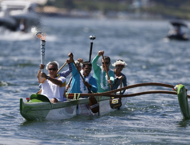 03.mai.2016 - Condutor carrega a tocha olímpica em um barco durante o revezamento em Brasília