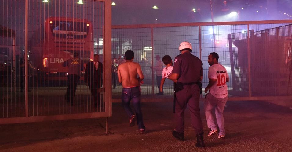 Torcedor é socorrido por policial militar durante chegada da delegação do São Paulo ao estádio do Morumbi para jogo contra o Atlético Nacional