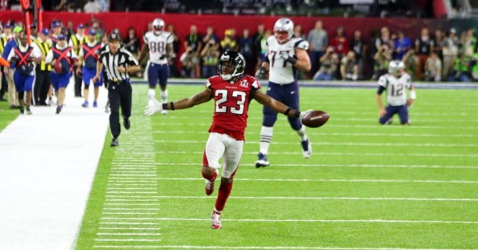 Robert Alford corre para anotar o terceiro touchdown dos Falcons após interceptar passe de Tom Brady, de joelhos ao fundos
