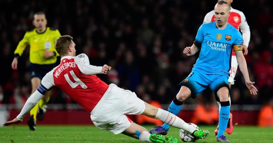 Mertesacker dá carrinho para roubar a bola de Iniesta na partida entre Arsenal e Barcelona pela Liga dos Campeões