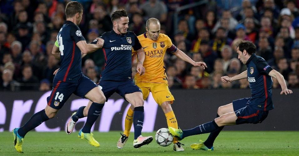 Iniesta é cercado por três jogadores do Atlético de Madri pela Liga dos Campeões