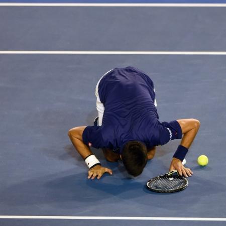 Djokovic beija o chão da Rod Laver Arena depois de ser campeão do Aberto da Austrália - GREG WOOD/AFP