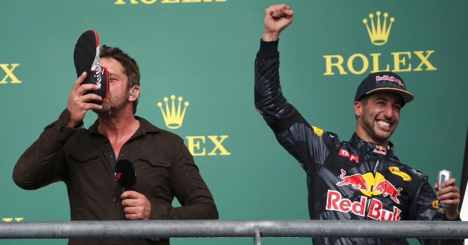 Ator Gerard Butler bebe champanhe da sapatilha de Daniel Ricciardo, da Red Bull, que terminou o GP dos EUA na terceira colocação