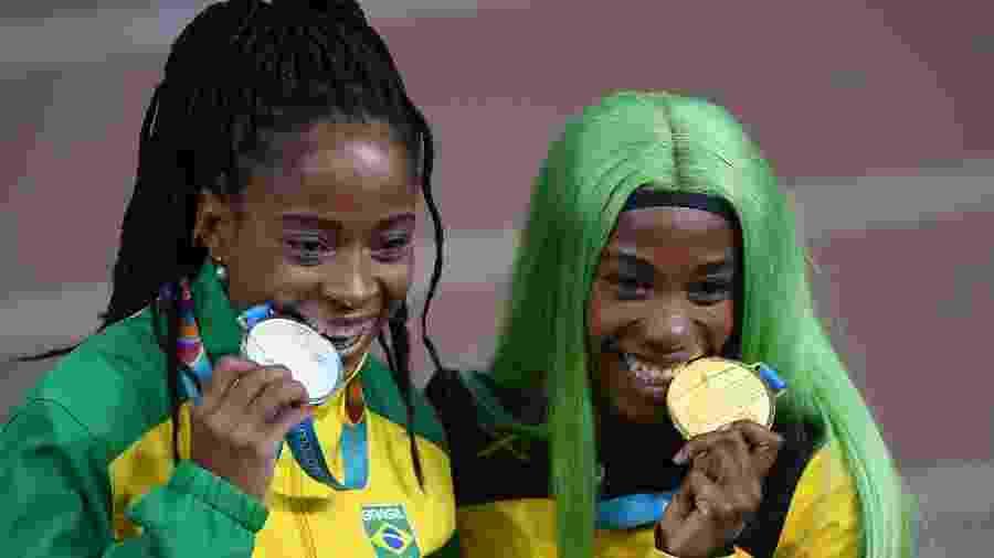 Vitória Rosa e a jamaicana Shelly-Ann Fraser-Pryce com as medalhas de prata e ouro dos 200 m no Pan - Pedro PARDO / AFP