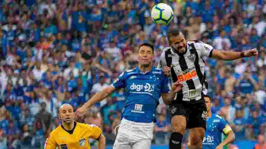 Thiago Neves e Zé Welison disputam bola na partida entre Cruzeiro e Atlético-MG, no Mineirão - Alessandra Torres/AGIF