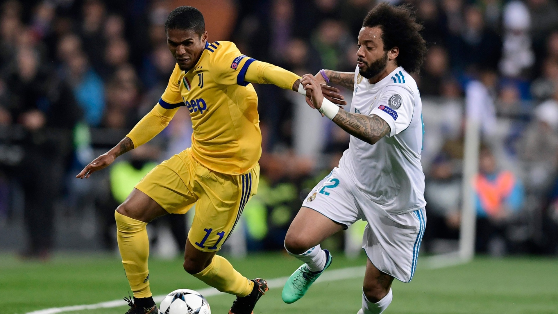 Douglas Costa tenta passar pela marcação de Marcelo, durante a partida entre Juventus e Real Madrid