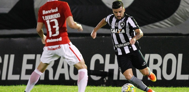 Victor Luis carrega a bola pelo Botafogo em jogo contra o Internacional no Brasileiro