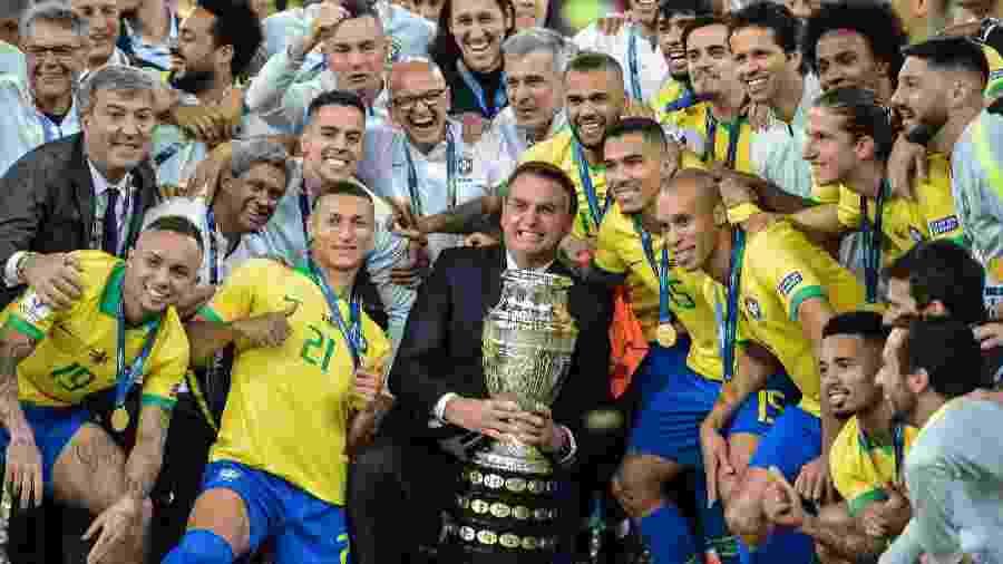 Bolsonaro sorri e posa com a taça da Copa América junto aos jogadores da seleção - Carl de Souza/AFP