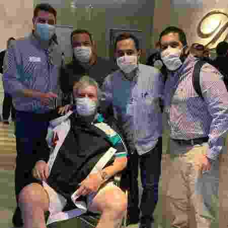 Clóvis, na cadeira de rodas, na saída do hospital acompanhado de seus companheiros de grupo político do Vasco - Divulgação