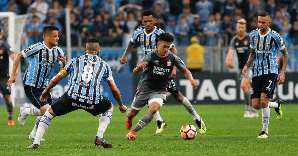 Lucas Rodríguez, do Estudiantes, tenta passar entre marcadores do Grêmio