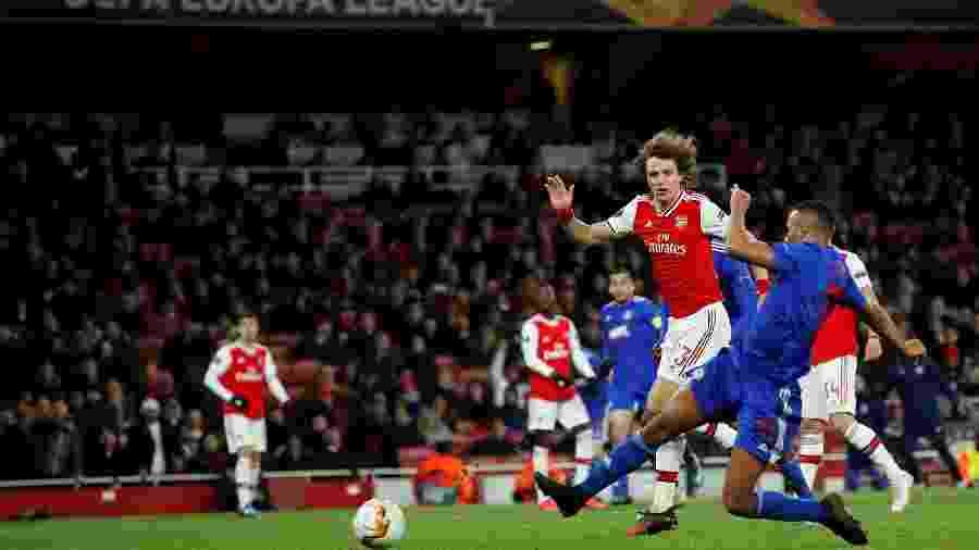 Youssef El-Arabi, do Olympiacos, à frente de David Luiz no lance que originou o gol diante do Arsenal pela Liga Europa - David Klein/Reuters