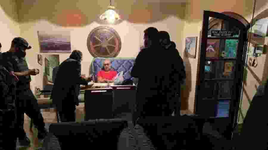 18.jun.2020 - Fabrício Queiroz (de vermelho), ex-assessor de Flávio Bolsonaro, no momento em que é preso pelos policiais dentro de um imóvel em Atibaia (SP). Queiroz estava há um ano escondido no local, que pertence ao advogado Frederick Wassef, próximo do clã Bolsonaro - Divulgação/Polícia Civil