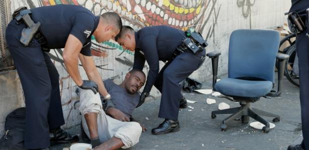 Policiais ajudam homem na região de Skid Row, local de grande concentração de moradores de rua