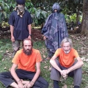 Rebeldes islamitas de Abu Sayyaf pediam US$ 12 milhões pelo resgate de Robert Hall (à dir.)