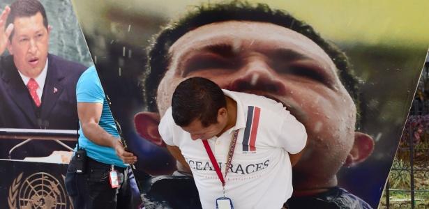 Funcionário da Assembleia Nacional da Venezuela retira fotos do ex-presidente Hugo Chávez do prédio que abriga o órgão legislativo