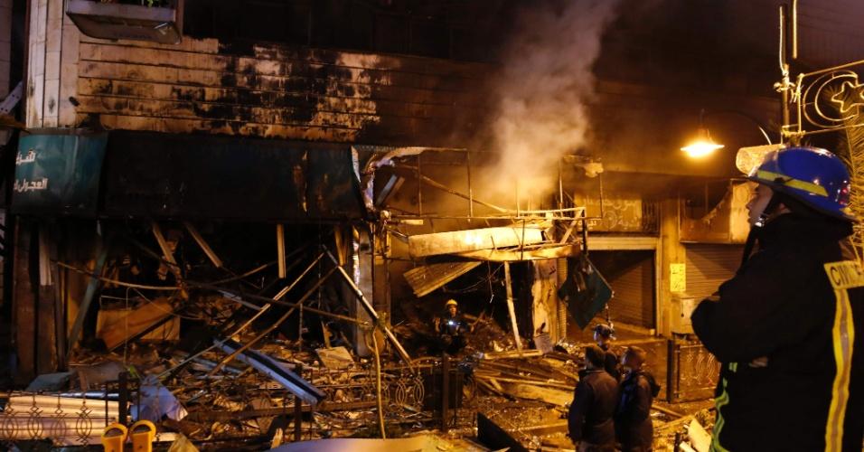 14.abr.2016 - Bombeiros palestinos combatem incêndio em casa de câmbio de Ramallah invadida e atacada por militares israelenses nesta madrugada. Um porta-voz do exército israelense alegou que o ataque visava